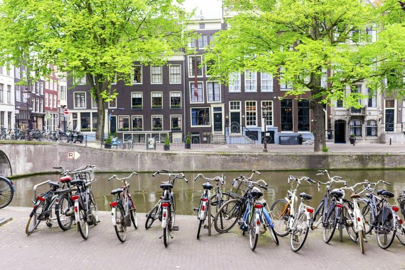 Overvloed van fietsen door het kanaal in Amsterdam, Netherlandes royalty-vrije stock foto's