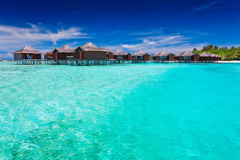 Overwater bungallows in blue lagoon. Around tropical island stock photography