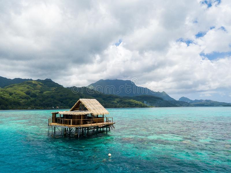 Lonely overwater bungalow of black pearl farmers. Blue azure turquoise lagoon. Raiatea island, French Polynesia. Aerial view. stock photo