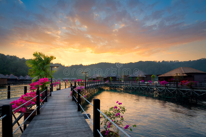 Overwater bungalow at dusk with beautiful sunset. Overwater bungalow at dusk.Beautiful sunset over beach with water villas in resort.Summer vacation concept royalty free stock photography