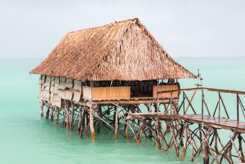 Overwater thatched roof bungalow hut of Micronesian people, lagoon of South Tarawa, heavy rain shower, wet season, Kiribati,. Traditional authentic overwater royalty free stock photo