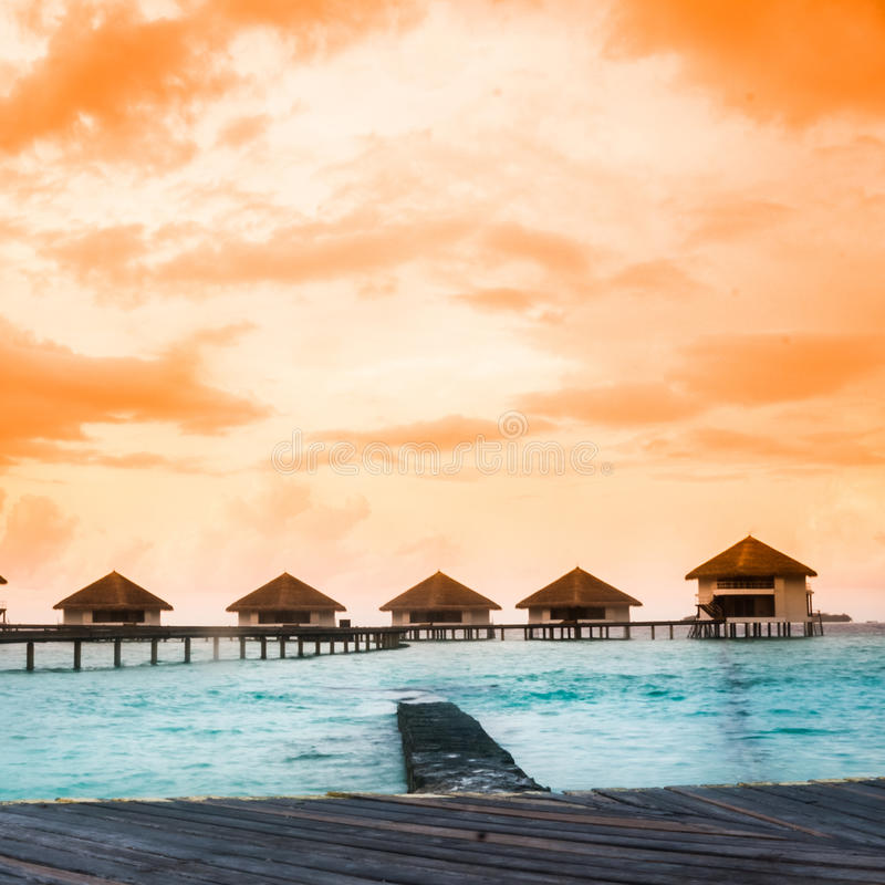Overwater villas in blue tropical lagoon. Of shallow water stock photo