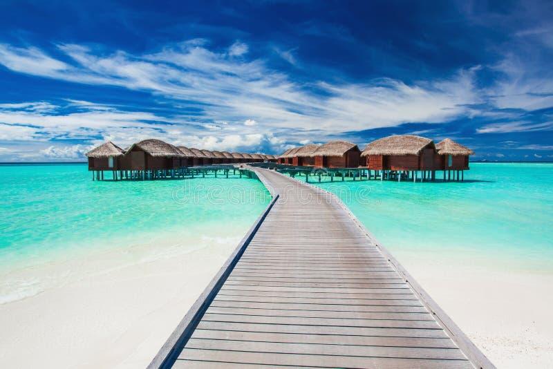 Overwatervilla's op de tropische die lagune door pier wordt verbonden royalty-vrije stock foto