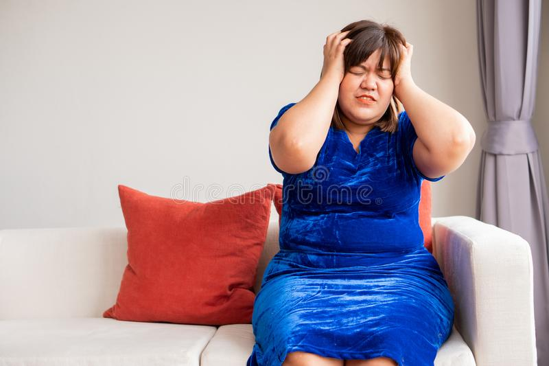An overweight Asian woman is sitting on the sofa in the living room. And holding hands in the head due to headaches from migraines royalty free stock photo