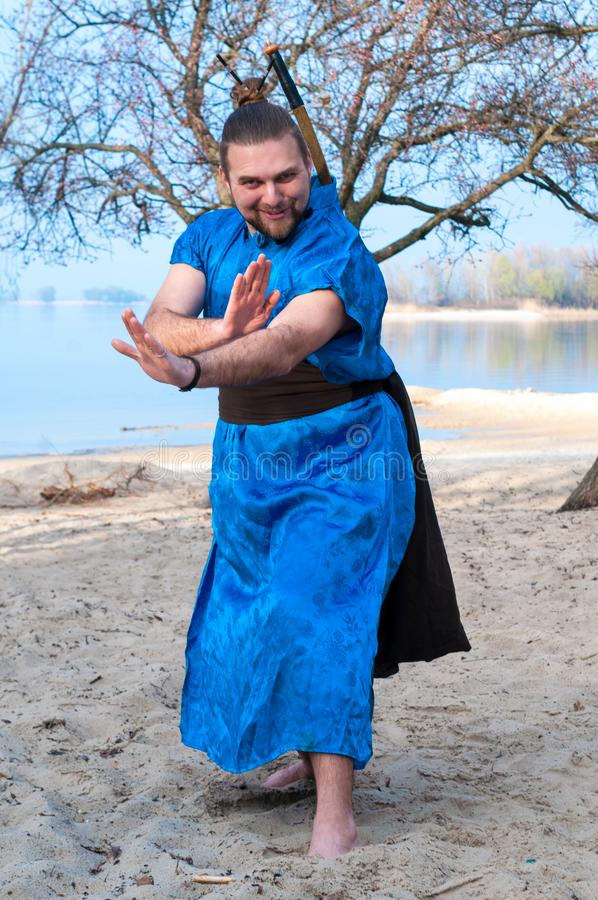 Overweight bearded samurai in blue kimono smiling and training with outstretched hands on sandy river beach royalty free stock images