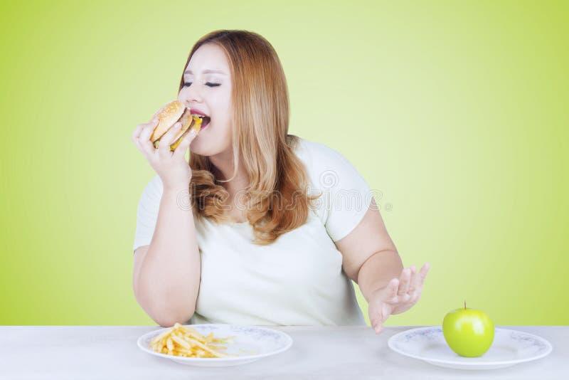 Overweight blonde woman eating hamburger. Portrait of overweight blonde woman rejecting a fresh apple fruit and choosing to eat hamburger stock images