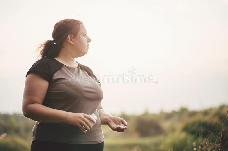 Overweight fat woman with a bottle of diet pills royalty free stock image