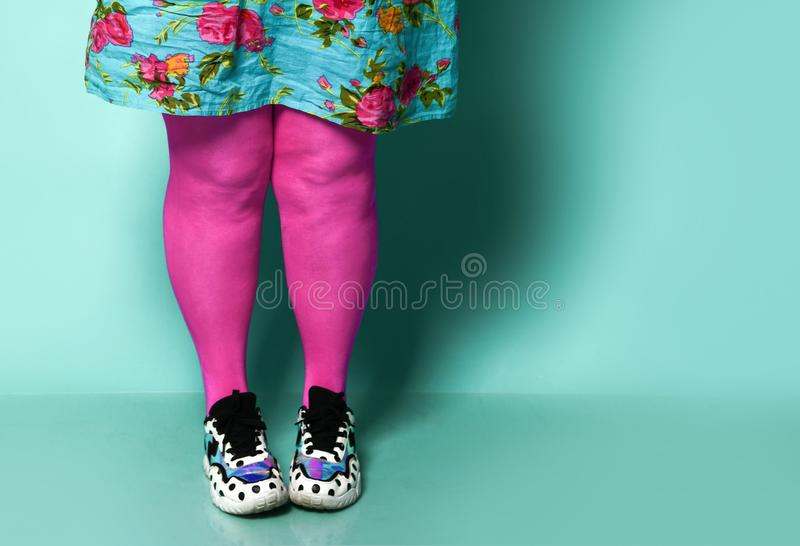 Overweight fat woman legs in modern pink leggings and sneakers close up royalty free stock photos