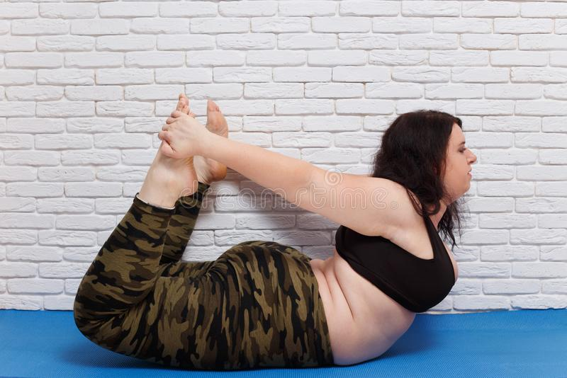 Overweight fat young woman doing yoga on mat at home. Fitness, s. Port, stretching, yoga, exercising, home workout, training and lifestyle concept royalty free stock images