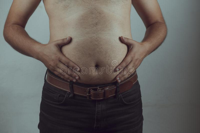 Overweight man closeup of belly front view. Man touching his fat belly - fat man & Diet, Belly Fat, junk, fast, obese, grabbing, stomach, checking, big, home royalty free stock image