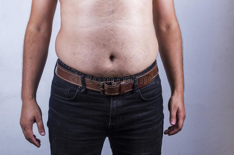 Overweight man closeup of belly front view - Man touching his fat belly. Diet, fast, obese, ruler, holding, grabbing, stomach, checking, big, home, unhealthy royalty free stock images
