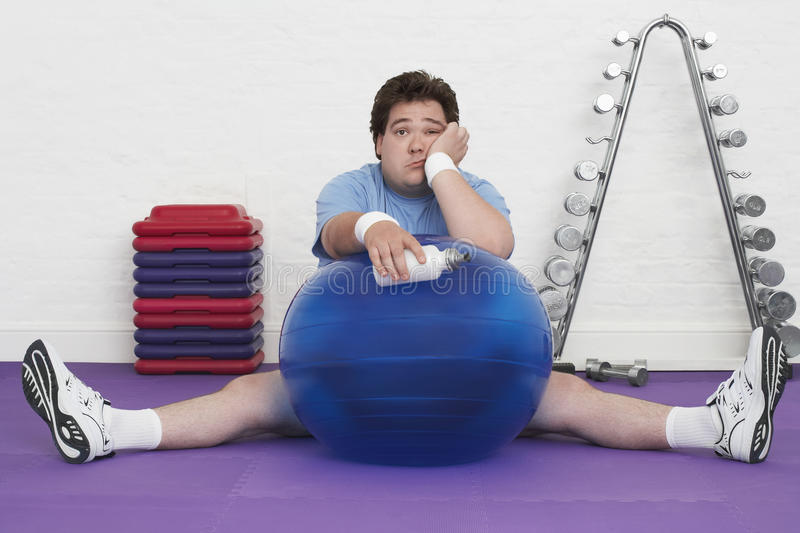 Overweight Man On Floor With Exercise Ball royalty free stock photography