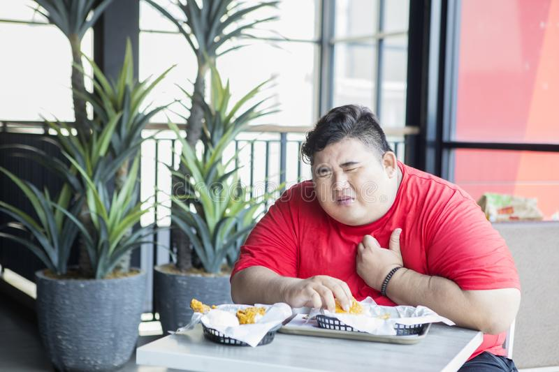 Overweight man getting heart attack in restaurant. Overweight man eating junk foods and looks getting heart attack while holding his chest in the restaurant royalty free stock images