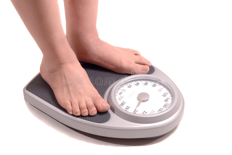 Overweight man on scale. Isolated image of an overweight man standing on a bathroom scale stock images