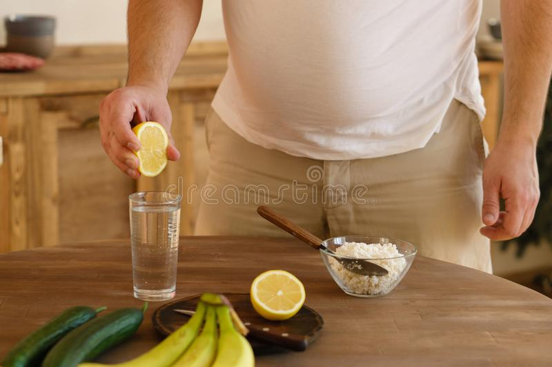 Overweight man squeezing lemon juice into water. Detox, hydration, metabolism boost, clean and healthy food concept. dieting, wellness, health care royalty free stock images