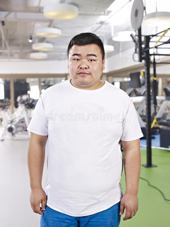 Overweight man standing in gym stock photos