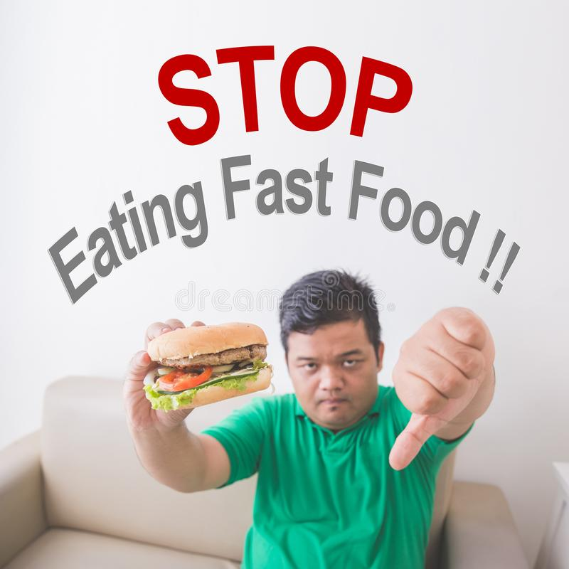 Overweight man stop eating junk food royalty free stock images