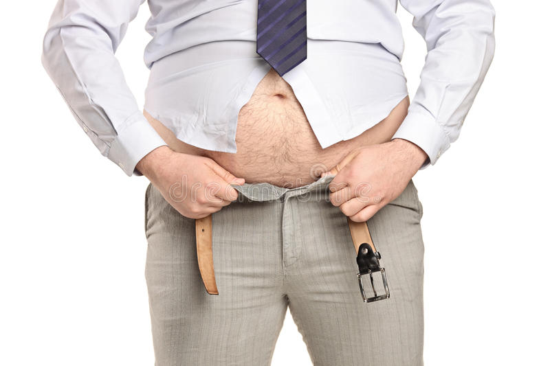 Overweight man trying to fasten too small clothes royalty free stock photography