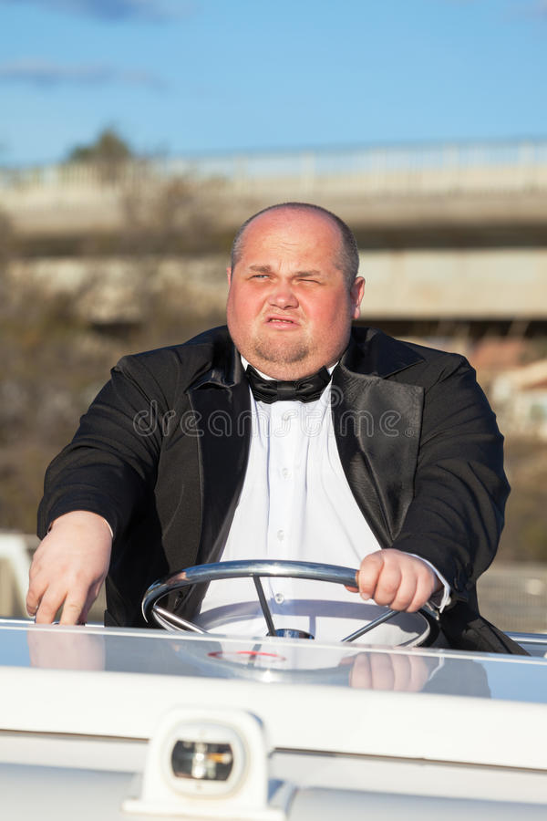Overweight Man In A Tuxedo At The Helm Of A Pleasure Boat Royalty Free Stock Photography