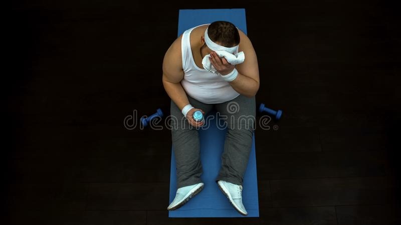 Overweight man wiping sweat from his forehead after exhausted training at gym stock photos