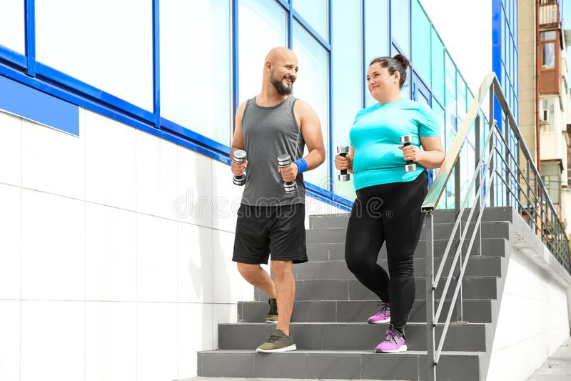 Overweight man and woman running with dumbbells royalty free stock photo