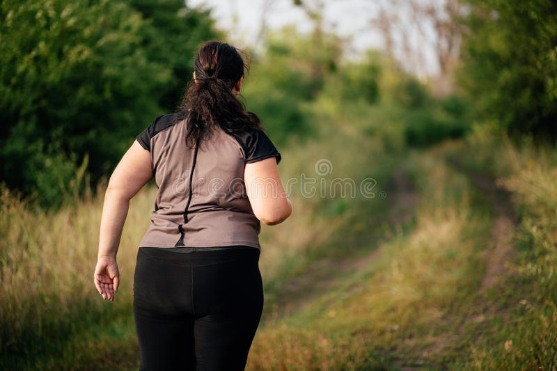 Overweight runner go jogging outdoors. Weight loss. Cropped portrait of overweight runner go jogging outdoors. Weight loss, sports, healthy lifestyle royalty free stock photos