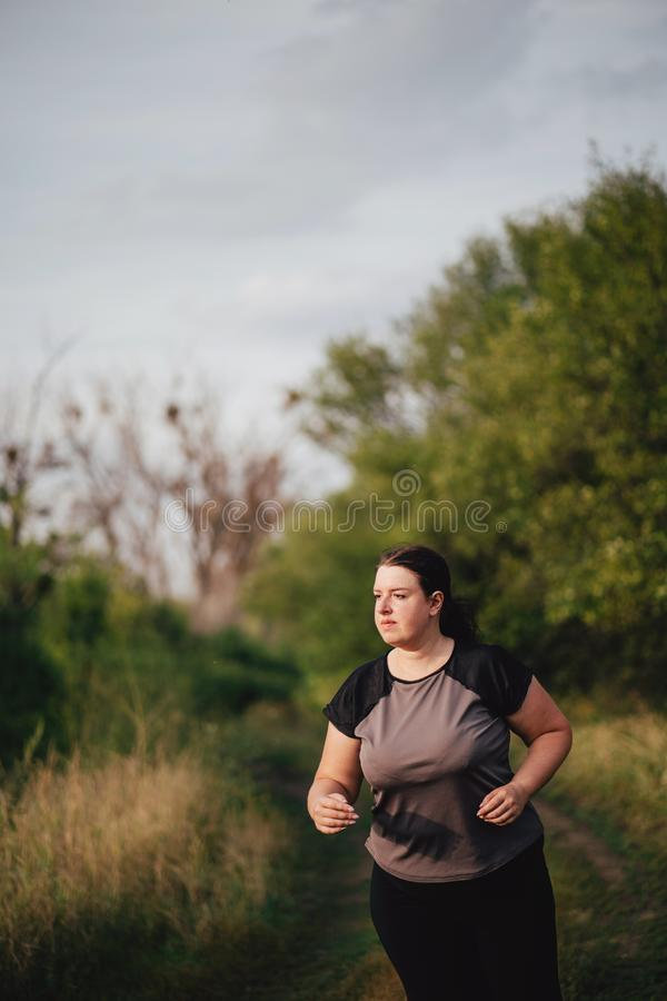 Overweight runner go jogging outdoors. Weight loss. Cropped portrait of overweight runner go jogging outdoors. Weight loss, sports, healthy lifestyle royalty free stock photography