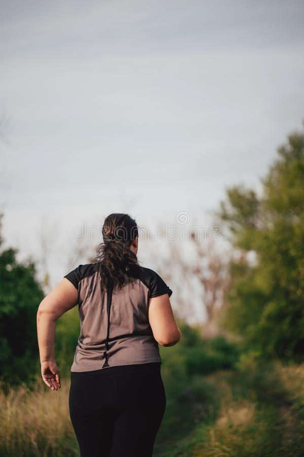 Overweight runner go jogging outdoors. Weight loss. Cropped portrait of overweight runner go jogging outdoors. Weight loss, sports, healthy lifestyle royalty free stock image