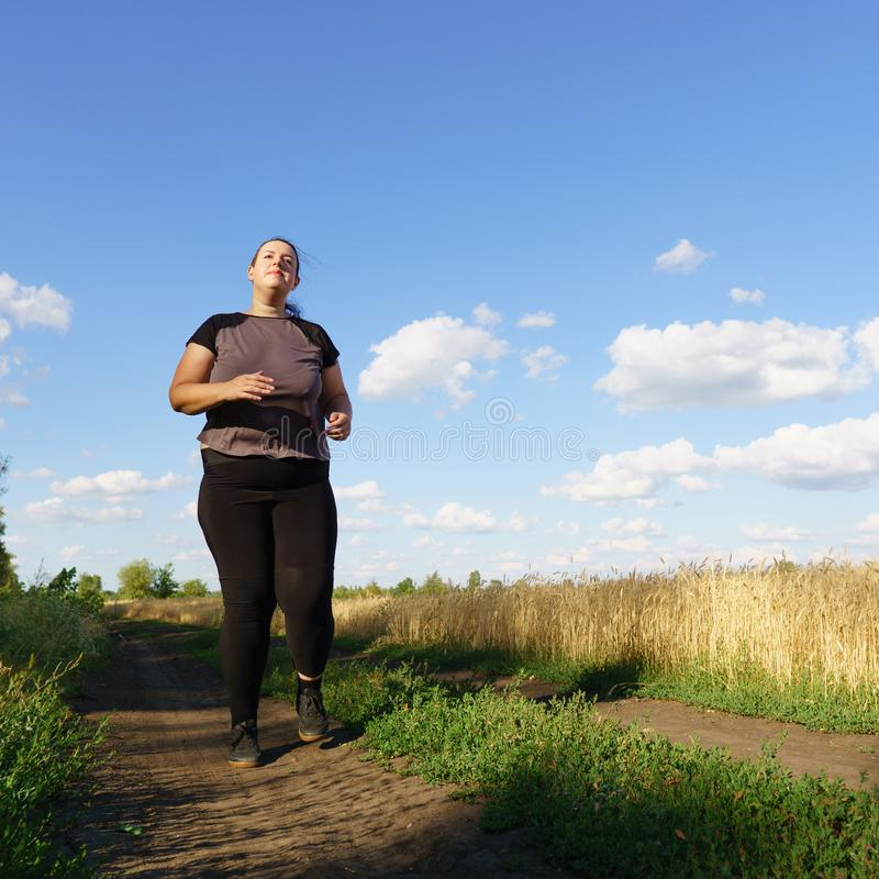 Overweight runner go jogging outdoors. Weight loss. Sports, healthy lifestyle stock photography