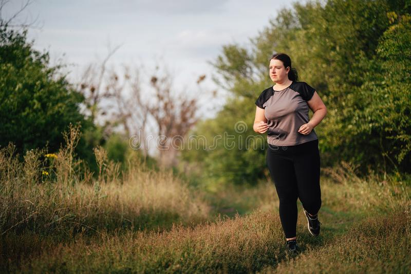 Overweight runner go jogging outdoors. Weight loss. Sports, healthy lifestyle stock photo
