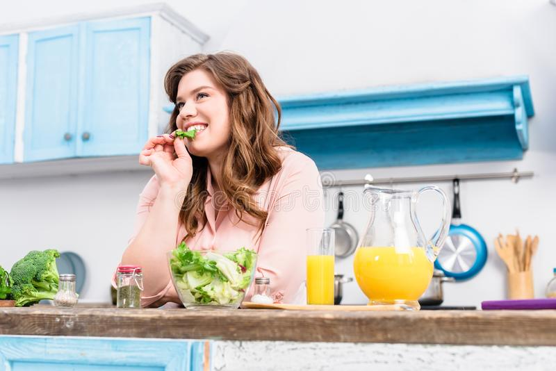 overweight smiling woman at table with fresh salad in kitchen royalty free stock image