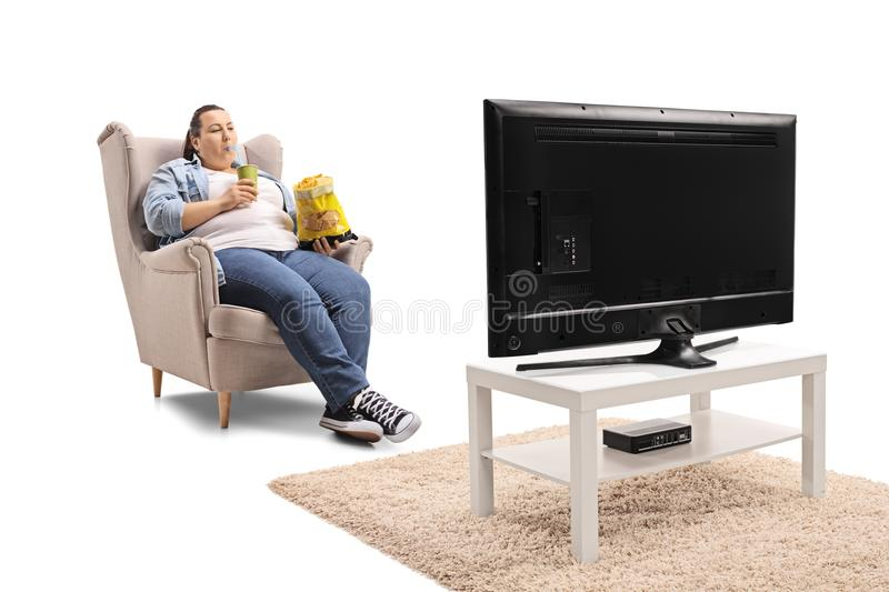 Overweight woman with a bag of chips and a drink sitting in an a royalty free stock photography