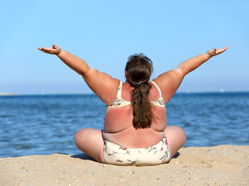 Overweight woman on beach with hands up royalty free stock photo