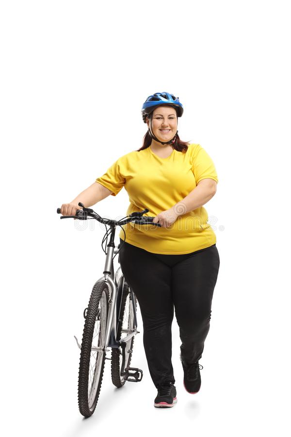 Overweight woman with a bicycle walking towards the camera. Full length portrait of an overweight woman with a bicycle walking towards the camera isolated on royalty free stock images