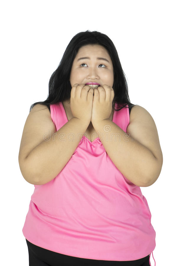 Overweight woman biting her fingernails. Portrait of overweight woman looks afraid while biting her fingernails, isolated on white background stock photos