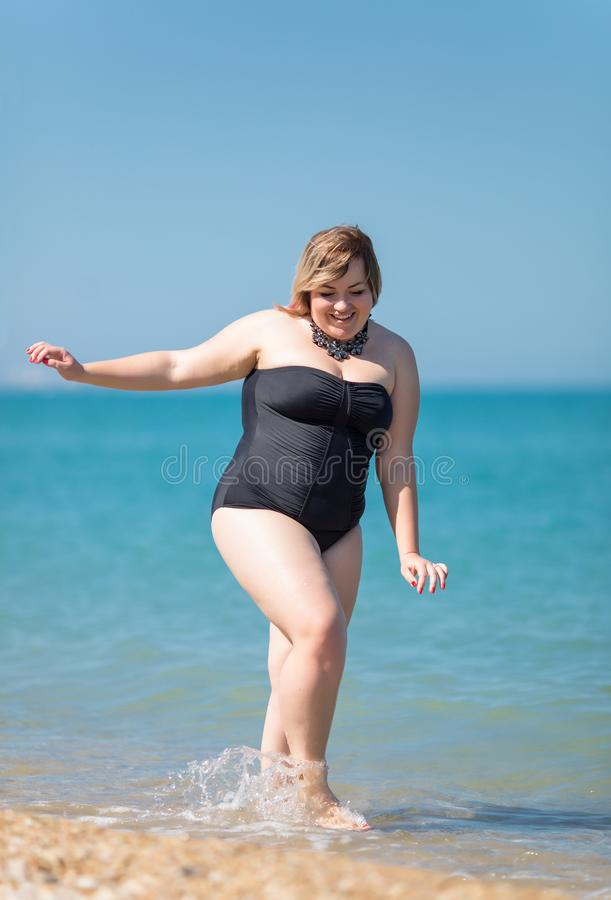 Overweight woman in black one-piece swimsuit comes from sea royalty free stock photography
