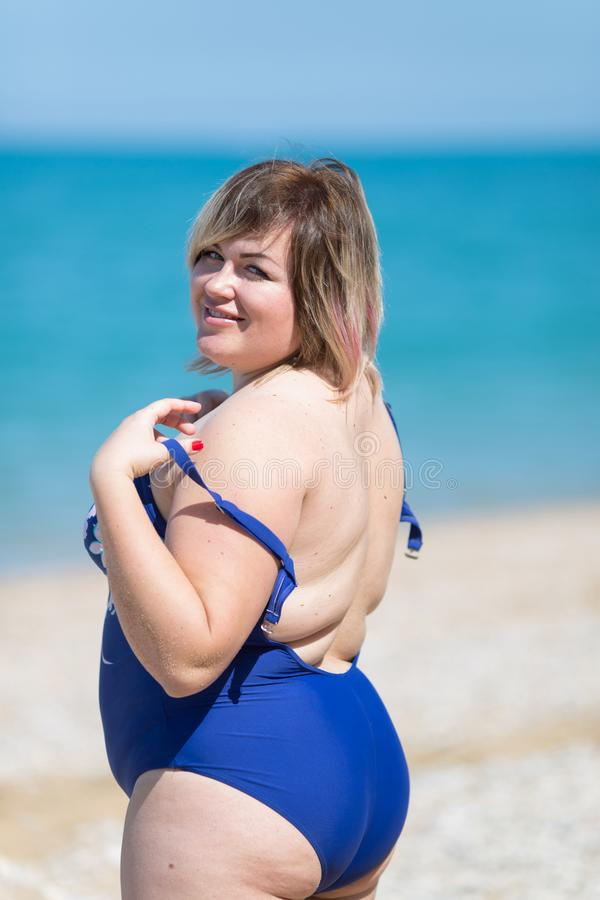 Overweight woman in blue one-piece swimsuit at the sea royalty free stock image