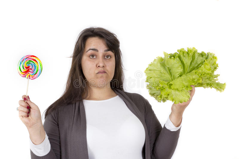 Overweight woman choice junk food and healthy. Large young woman decided for unhealthy or healthy food on white background royalty free stock photography
