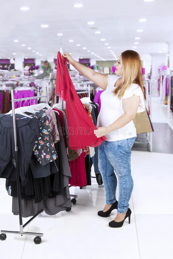 Overweight woman choosing a clothes royalty free stock photos