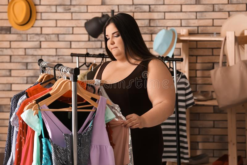 Overweight woman choosing clothes in shop royalty free stock photos