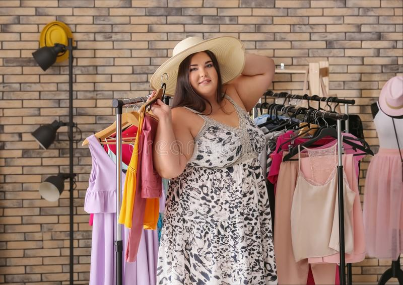 Overweight woman choosing clothes in shop stock image