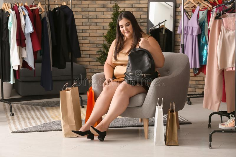 Overweight woman choosing shoes in shop stock photography