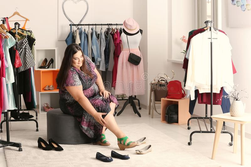 Overweight woman choosing shoes in shop royalty free stock photography