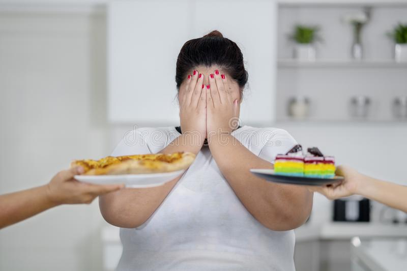 Overweight woman close her eyes avoid junk food stock photo