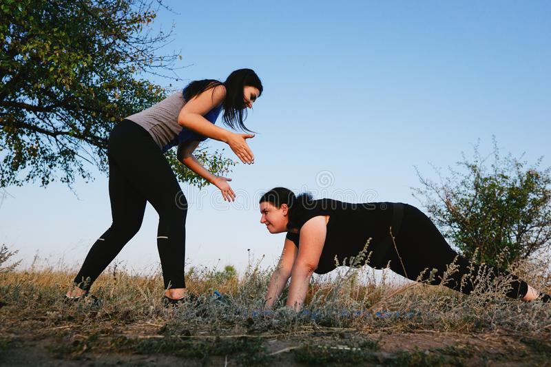 Overweight woman do pushups exercise with trainer. Personal trainer working with her client outdoors. Overweight women doing pushups on mat with assistance of stock photo