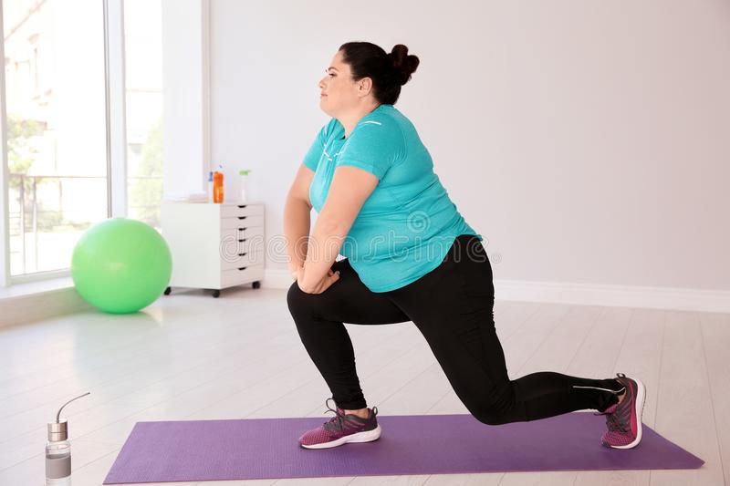 Overweight woman doing exercise on mat royalty free stock photography
