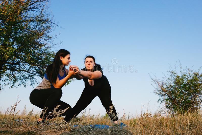 Overweight woman doing lateral lunges. Overweight women with personal trainer doing lateral lunges. Fitness, sport, weight loss, training, teamwork and lifestyle royalty free stock photography