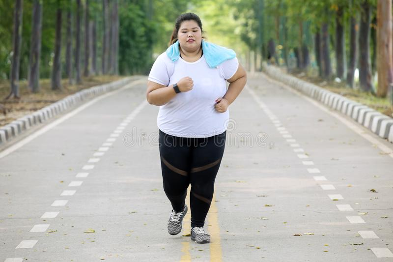 Overweight woman doing runs exercise on the road stock image