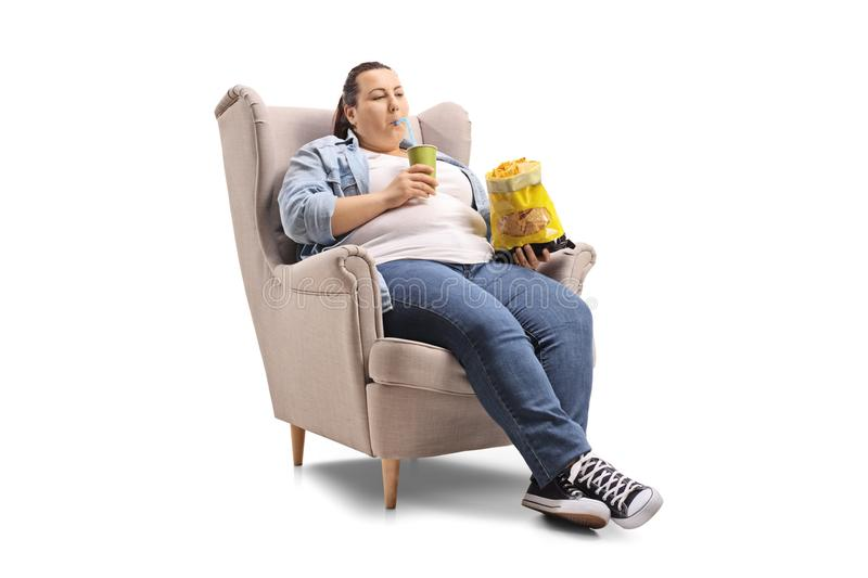Overweight woman with a drink and a bag of chips sitting in an a. Rmchair isolated on white background royalty free stock photography