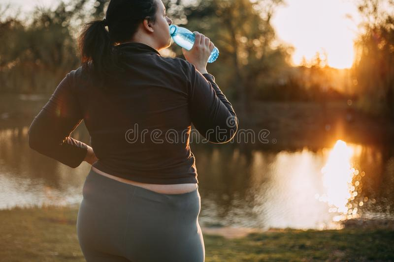 Overweight woman drink water during morning walk stock photo